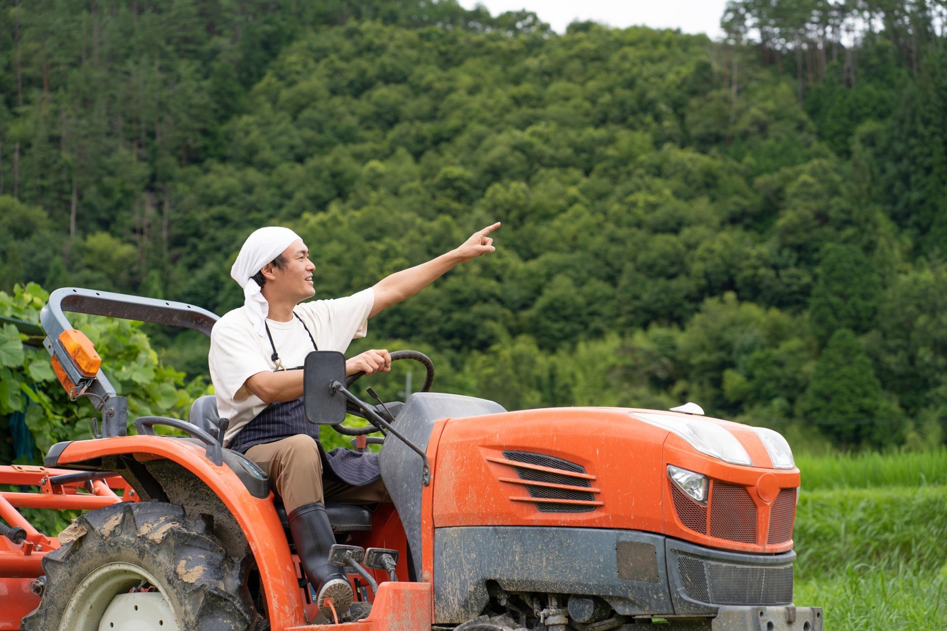 トラクターに乗った男性が指をさしている