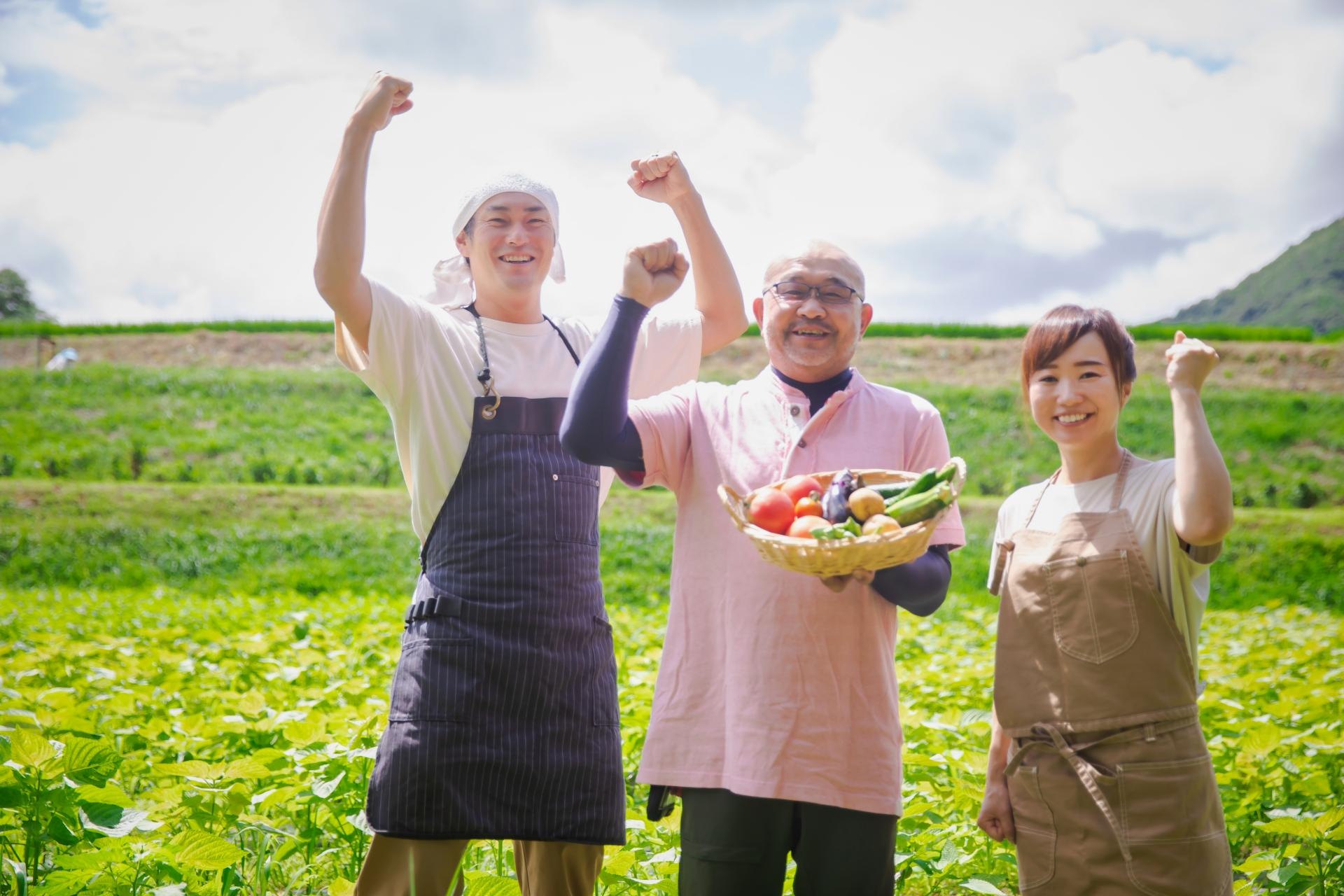 男女3人が畑の前でガッツポーズしている